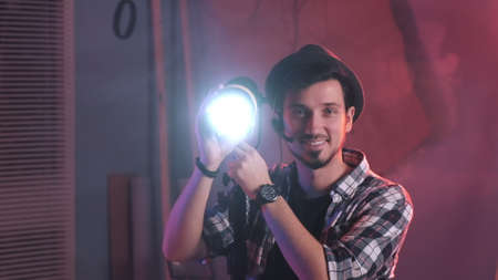 Close-up of key grip turning lamp to the camera and starting smiling. There is red light in film studio.