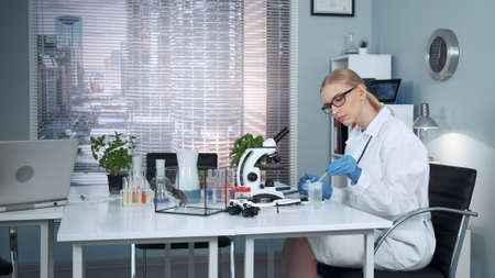 In modern chemistry lab female research scientist using pipette to drop fertilizers on slider and then examining it under magnifying glass Stock Photo