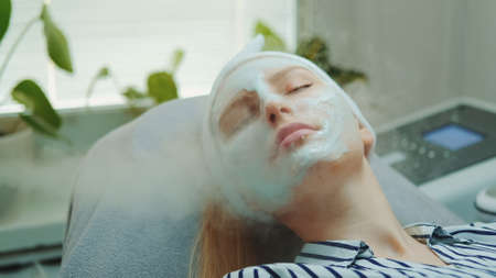 Medium close-up shot of professional facial skin care treatment with a cosmetic steamer at beauty salon. The Steam cleaning procedure of the face.