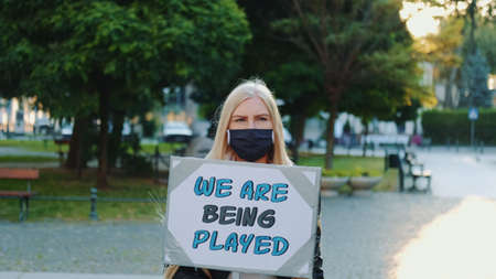 Pretty girl wearing medical mask protesting against authorities that playing human lives. She walking alone in the downtown.