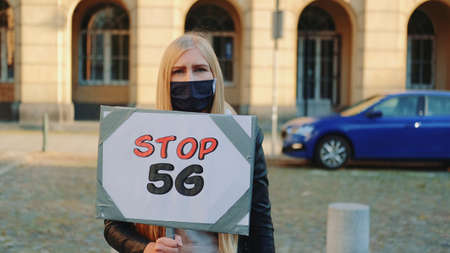 Young woman in protective mask protesting against 5G internet by walking on the street with steamer.