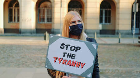 Young woman in protective mask calling to stop the tyranny by holding steamer. Protest walk in the city center. Stock Photo