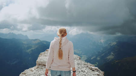 Back view of blonde woman walking on the top of the mountain under the clouds. Stunning view