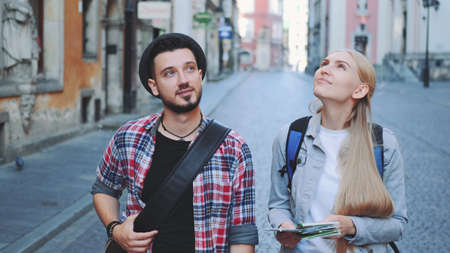Happy young tourist couple with map walking and looking at old city architecture. Sightseeing in beautiful european city. Banco de Imagens