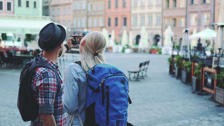Back view of young tourists couple making selfie on smartphone in the city center. They have tourists bags. Banco de Imagens