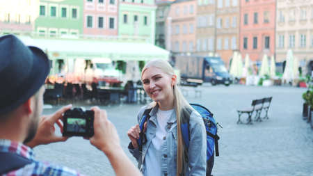 Medium shot of man making photos of female tourist on the view of city market square. Blonde woman making faces and smiling. Banco de Imagens
