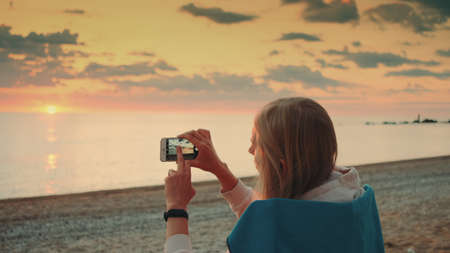 Young woman making video of sunset with smartphone sitting on the seashore. Back view