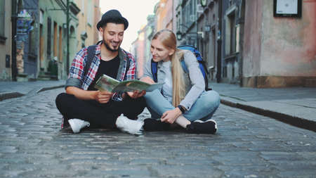 Young tourists couple using map, sitting on pavement and admiring historical surroundings. They are excited and smiled.