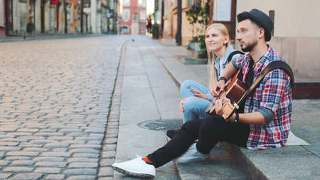 Man and woman sitting on sidewalk, playing guitar and having rest. Sightseeing in beautiful european city.