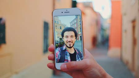 Close-up of hand holding smartphone during video call with man in front of the sea. In the background - old town. Banco de Imagens