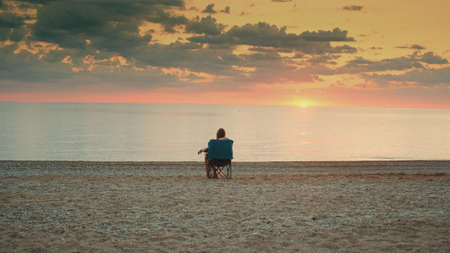 View of lady admiring sunset on the sea sitting in folding tourist chair. Relaxing and enjoying nature. Banco de Imagens