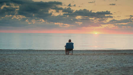 Back view of woman admiring sunset on the sea sitting in folding tourist chair. Relaxing and enjoying nature.