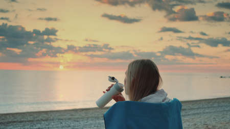 Young woman drinking from thermal mug and sitting on the beach before sunrise. Back view.