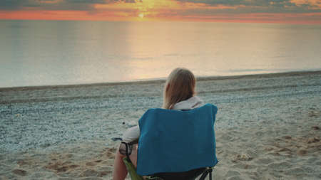 Woman drinking from thermal mug and sitting on the beach before sunrise. Back view.