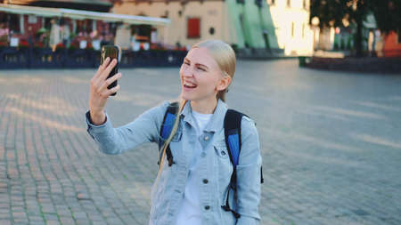 Female tourist making video call on smartphone from the place of her visit. Sightseeing in beautiful european city.