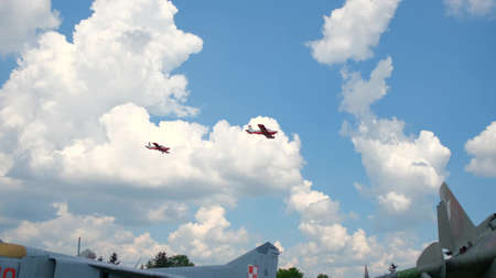 Two small airplanes flying thorough the sky. A mixture of clouds and blue sky provides a great backdrop.