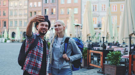 Couple of tourists making selfie on smartphone in the city center. They have tourists bags.