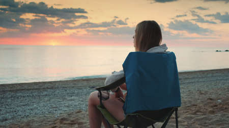 Woman drinking from thermos and sitting on camping chairs on the beach. Back view.