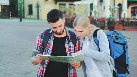 Tourists couple holding map for finding new interesting place for sightseeing. They standing on city square. Banco de Imagens