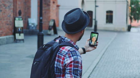Back view of young tourist making video call on smartphone with female tourist from other place. They exchanging impressions from travelings. Banco de Imagens