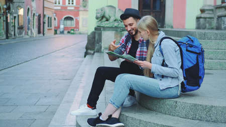 Tourist couple sitting on street stairs, checking city map and discussing. In the background there is beautiful old town view.