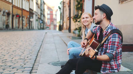 Tourists sitting on sidewalk, playing guitar and having rest. Sightseeing in beautiful european city. Banco de Imagens