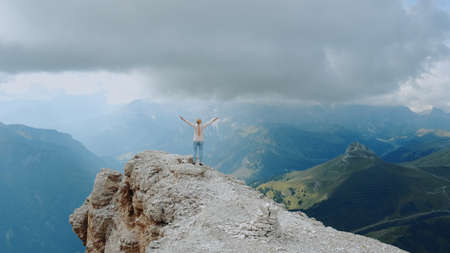 Fantastic landscape of mountain rocks and woman standing on the top with outstretched hands. Freedom concept.