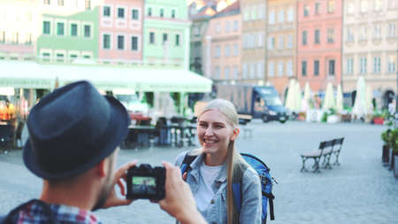 Back view of man making photos of female tourist on the view of city market square. Blonde woman making faces and smiling.