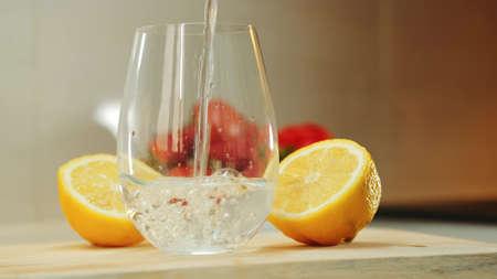 Empty glass between two part of cut lemon on wooden cutting board. Close up shot Banco de Imagens