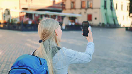 Back view of female tourist making video call on smartphone with her friend from other place. They exchanging impressions from travelings.
