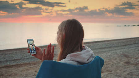 Young woman making video call with smartphone on the seashore. She speaking with young man.