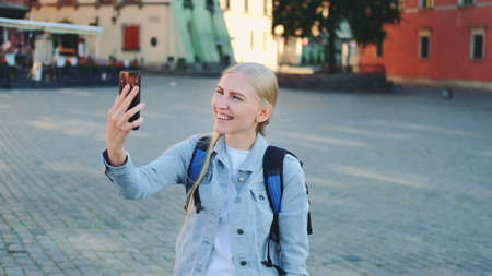 Pretty female tourist making video call on smartphone from the place of her visit. Sightseeing in beautiful european city. Banco de Imagens