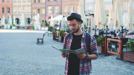 Zoom shot of trendy young tourist with map smiling to the camera. He standing on big market square.