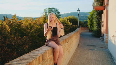 Positive blonde woman making video call with smartphone from the place of her visit. Summer time in other country.