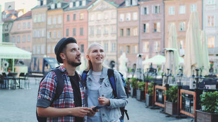 Young couple of tourists using smartphone and admiring beautiful surroundings. They going sightseeing early in the morning.