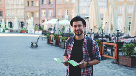 Zoom shot of trendy tourist with map smiling to the camera. He standing on big market square.