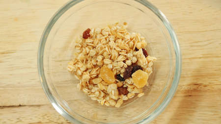 Pouring muesli breakfast mix in bowl. Close up shot Banco de Imagens