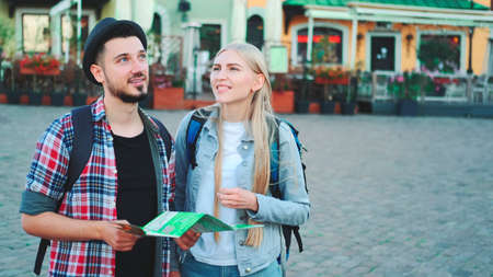 Trendy couple of tourists finding necessary destination on map and admiring surroundings. They standing on city square. Banco de Imagens