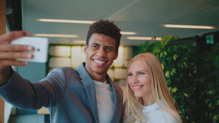 Cheerful black man with laughing blond woman taking selfie with smartphone in modern office having fun.
