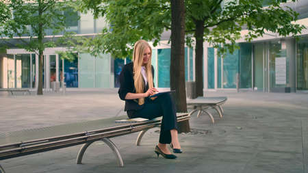 Formal business woman sitting on bench in office patio and browsing tablet in leisure. Banco de Imagens