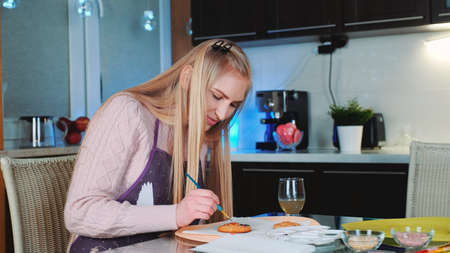 Beautiful woman painting sweet cookies with special food colors in the kitchen. Cooking traditions concept.