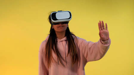 Multiracial girl using virtual reality glasses while standing against yellow background. Banco de Imagens