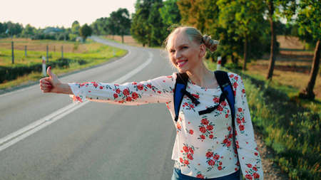 Traveler woman hitchhiking on a sunny road and walking. Young happy backpacker woman looking for a ride to start a journey on a sunlit country road.