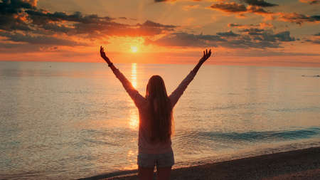 Young woman with outstretched arms enjoying the beauty of sunset on the sea. Crane shot. Banco de Imagens