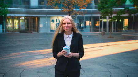 Elegant blond woman in suit and with long hair drinking coffee from white cup in patio with trees. Banco de Imagens