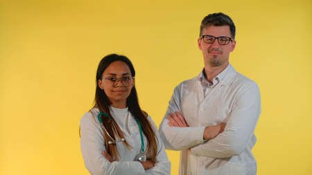 Multiracial male and female doctors nodding their heads to the camera on yellow background. They are in eyeglasses and lab coats.