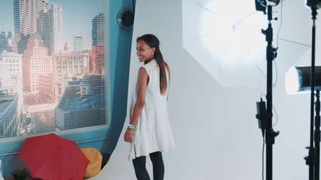 Photo shoot of stylish black model in modern professional studio photo shoot. Woman posing on camera. Banco de Imagens