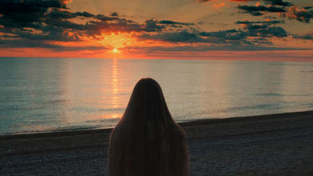 Close-up shot of girl with long hair walking to the sea and raising her hands up. Looking on sunset. Back view.