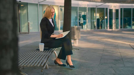 Side view of elegant businesswoman sitting on bench in patio and writing in notepad while working.