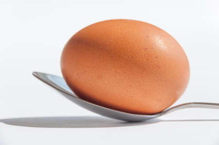 An egg on a spoon on white  photo